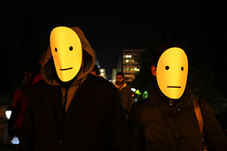 Masked protesters stand in front of the parliament in Athens