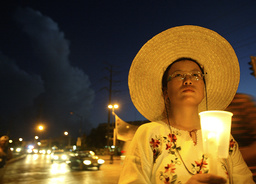 WOMAN HOLDS CANDLE AT CELEBRATION OF COLLPASE OF CANCUN WTO TALKS