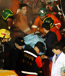 SOUTH KOREAN FIREMEN CARRY AN INJURED PERSON FROM A DESTROYED FOUR-STORY APARTMENT BUILDING IN INCHON