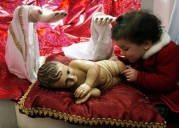 A child touches a statue of Baby Jesus in Bethlehem