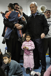 Israel's President Peres stands with children during visit to bomb shelter in Ashkelon