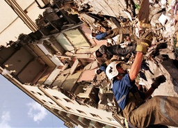THE RESCUE WORKERS CLEAN DEBRIS OF AN APARTMENT BUILDING DAMAGED BY GAS EXPLOSION