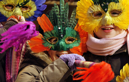 Children with a mask blow trumpets as they wait for New Year's Eve festivities to begin in Budapest