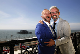 GGay couple Wale and Allard laugh as they pose in their hotel after marrying in the first same-sex wedding in Brighton, southern England