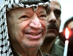 PALESTINIAN PRESIDENT YASSER ARAFAT LIGHTS A CANDLE DURING A CHRISTMAS CEREMONY IN RAMALLAH