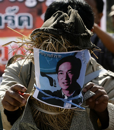A supporter of Thailand's ousted PM Thaksin places a photo of new PM Abhisit in front of an effigy in Udon Thani province