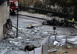 Firefighters and police officers check damage on the headquarters of the Basque ETB television following a car bomb blast in Bilbao