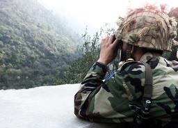 A PAKISTANI SOLDIER LOOKS THROUGH HIS BINOCULAR IN PAKISTANI CONTROLLED KASHMIR
