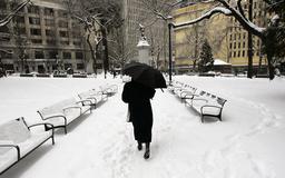 A pedestrian walks through a snow covered park in downtown Portland, Oregon