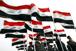 Policemen hold Iraqi national flags during their graduation ceremony in Baghdad