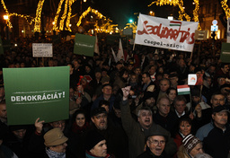 People hold up signs during a protest in central Budapest