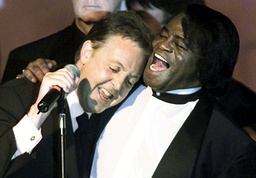 File photo of Paul McCartney being embraced by soul legend James Brown during a jam session in New York City