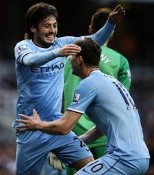 David Silva L of Manchester City celebrates scoring with teammate Edin Dzeko during the Barclays P