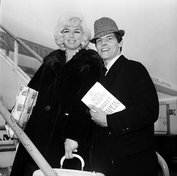 DIANA  DORS AND ACTOR-SINGER JESS CONRAD PICTURED AT LONDON AIRPORT ON THEIR WAY TO THE UNITED STATES. CONRAD IS FLYING TO HOLLYWOOD TO DO MPROMOTION WORK ON HIS FILM THE AMOROUS ADVENTURES OF  MOLL FLANDERS. 3TH FEBRUARY 1965.