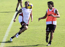 AC Milan's new loan signing Beckham chases the ball with teammate Mathias during a training session at Al Nasr Stadium in Dubai