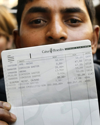Shalim Ahmed, from Bangladesh, shows his account bank book after depositing a winning ticket of 'El Gordo' as he celebrates in front of a lottery office in Barcelona