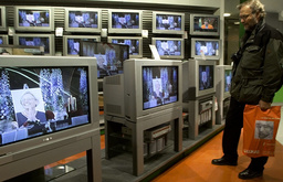 MAN WATCHES ANNA LINDH MEMORIAL CEREMONY IN TV STORE IN STOCKHOLM