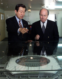 PARK SEH-JIK SHOWS A MODEL OF THE WORLD CUP STADIUM TO BLATTER