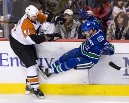 Philadelphia Flyers' Alberts knocks Vancouver Canucks' Sedin on his feet during the first period of NHL hockey game in Vancouver
