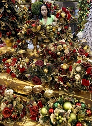 A woman arranges her Christmas decoration displays at a bazaar in Manila