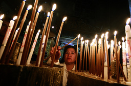 Christian pilgrim lights candle after Christmas mass at Church of Nativity in Bethlehem