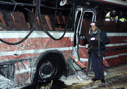 AN ISRAELI POLICEMAN WALKS IN FRONT OF A BUS AT THE SCENE WHERE PALESTINIAN GUNMEN KILLED AT LEAST 10 ISRAELIS