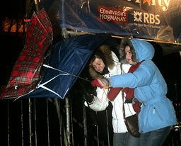 Tourists from New York in the U.S. struggle to control their umbrellas in the strong winds as they walk along Princes Street in Edinburgh