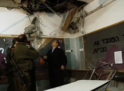 Israel's Defence Minister Barak surveys a damaged classroom after a rocket landed in a school in Beersheba