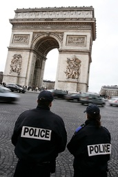 Policemen keep watch ahead of new year celebrations near the Arc de Triomphe on the Champs Elysees Avenue in Paris