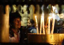 Worshipper lights candle after Christmas mass in Bethlehem