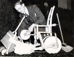 Heath Robinson Puts The Final Touches To A Combined Lawn-mower And Roller In The Garden Of His Whimsical House At The 1934 Daily Mail Ideal Home Exhibition
