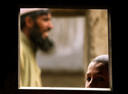 AFGHAN BOY LOOKS THROUGH WINDOW OF SCHOOL FOR STREET CHILDREN IN KABUL.