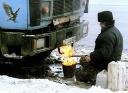 A RUSSIAN TRUCK DRIVER HEATS UP A DIESEL ENGINE