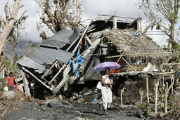 A villager carries her son past a ruined house in Padang village