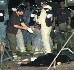 ISRAELI POLICEMEN CHECK BODY OF A VICTIM OF A SUICIDE BOMBING IN RISHON LETZION