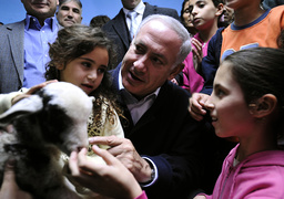 Likud party leader Netanyahu speaks with children during a visit to a bomb shelter in Ashkelon