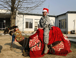 U.S. soldier tries to ride camel as part Christmas celebrations at Camp Eggers in Kabul