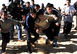 PALESTINIAN YOUTHS CARRY WOUNDED BOY DURING CLASHES IN GAZA STRIP