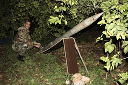 Lebanese soldier inspects one of eight rockets found in a field in Naqoura village