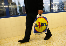 A customer carries a plastic bags after shopping at a Lidl supermarket in Berlin
