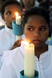 AN EAST TIMORESE GIRL HOLDS A CANDLE DURING A MASS PRAYER SERVICE IN TACITOLU