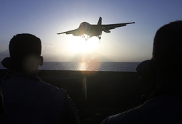 AIRCRAFT CARRIER CREW MEMBERS WATCH AN FA18 FIGHTER LAND ON USS CARL VINSON