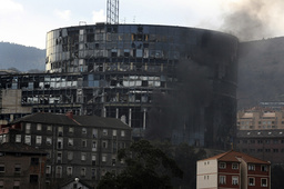 Smoke rises in front of a damaged building following a car bomb blast in Bilbao.