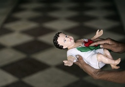 A worker cleans a figure of baby Jesus at a church ahead of Christmas in Siliguri