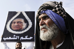 Anti-Mubarak protesters hold up a placard depicting former President Mubarak with a noose, in front of the police academy where Mubarak is on trial in Cairo