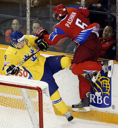 Team Russia's Pashnin hits Team Sweden's Moller into the boards during their hockey game at the 2009 IIHF U20 World Junior Hockey Championships in Ottawa