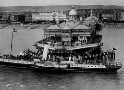 Eastbourne Pier In Sussex England. Passengers Landing On Eastbourne Pier After A Boat Cruise.