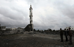 Palestinians look at mosque destroyed after an Israeli air strike in Gaza
