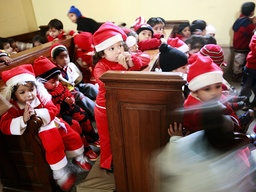 Schoolchildren dressed as Santa Claus sit and stand in a church ahead of Christmas in New Delhi