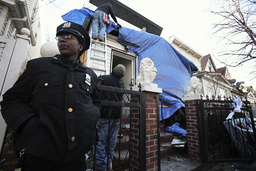 A New York CIty police officer stands outside a residence that was hit with a firebomb in the Queens borough of New York